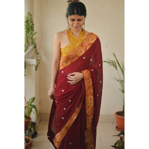 Chiffon saree with embroidered border and hand embroidered motifs in beads pearls.