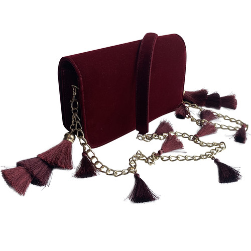 Side view of the TASSIE burgundy velvet crossbody bag with tassels