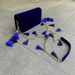 Lifestyle shot of TASSIE royal blue velvet crossbody bag with tassels