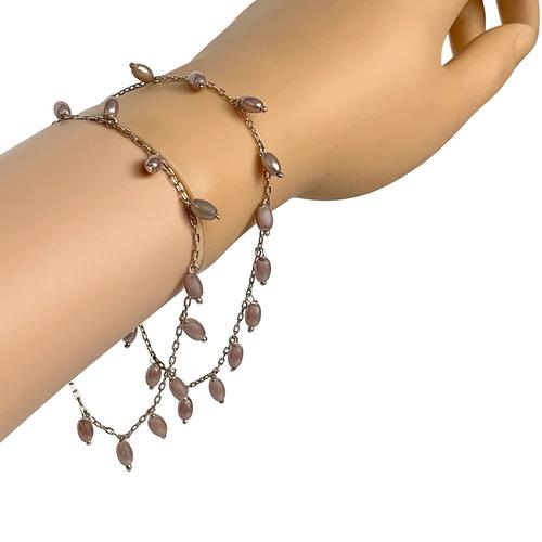 Model wearing two RIZZO grey rice pearl bracelets on wrist