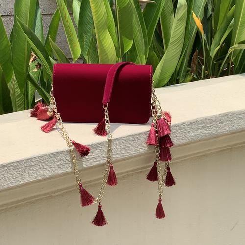 Lifestyle shot of the TASSIE ruby velvet crossbody bag with tassels