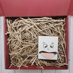 Red gift box filled with brown shredded paper. On the bottom right is a small white box of a cartoon face with a stuck-out tongue. The tongue shows the socks toe.