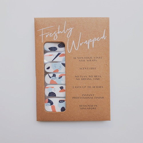 Brown rectangle paper packaging of a nail wrap. The nail wrap has five different design for each finger nail. The nail wrap has a clear transparent base with abstract patterns in solid blue, white and coral. The words Freshly Wrapped can be seen on top of the packaging.