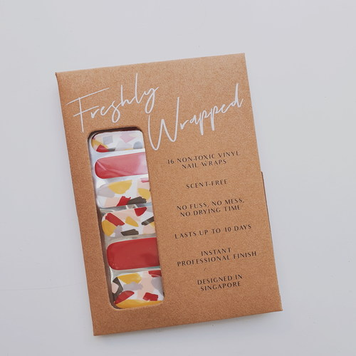 Brown rectangle paper packaging of a nail wrap. The nail wrap is made up of two designs. The nails for the index finger and thumb are red while the rest of the fingers have an abstract brush pattern in white, yellow, light grey, dark grey and red. The words Freshly Wrapped can be seen on top of the packaging.