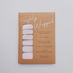 Brown rectangle paper packaging of a nail wrap. The nail wrap has a light pink base with a clear triangular bottom with white horizontal stripes. The words Freshly Wrapped can be seen on top of the packaging.