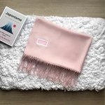 Folded baby pink shawl with fringes below. A small pink textile with white frame sewn on the left side of the shawl says Corporate Cuddles.