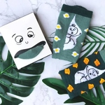 On the left is a small white box of a cartoon face with a stuck-out tongue. The tongue shows a green sock toe. In the middle is a folded sock with light green leg and dark green cuff. There are eggs graphics spread all over the sock, with a stick man graphic printed against a white background at the leg region. On the right is a folded sock with a dark green leg and light green cuff. There are yellow toast graphics spread all over the sock, with a stick man graphic printed against a white background at the leg region.