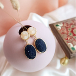 A pair of gold rimmed dangle earrings with a round white quartz on top and an oval dark blue quartz below.