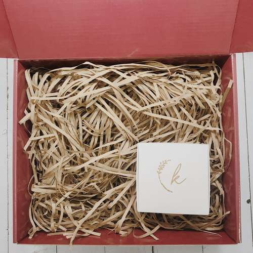Red gift box filled with brown shredded paper. On the bottom right is a small white box with a K logo.