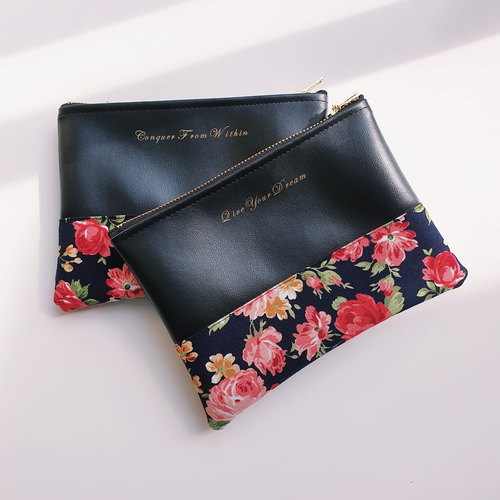 Two black clutches stacked on top of each other. The clutches have different quotes printed in gold with floral prints on the bottom half and a gold zipper.