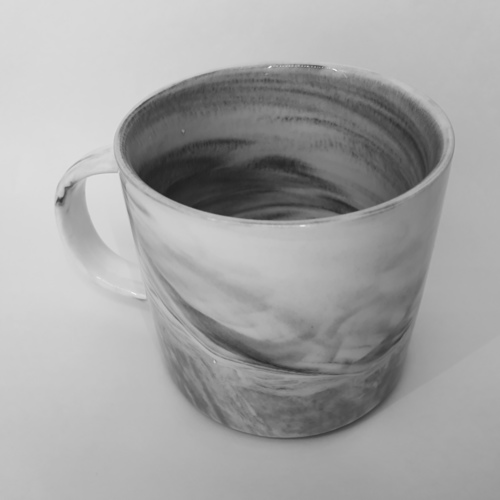 A blue gray marbled mug with handle.