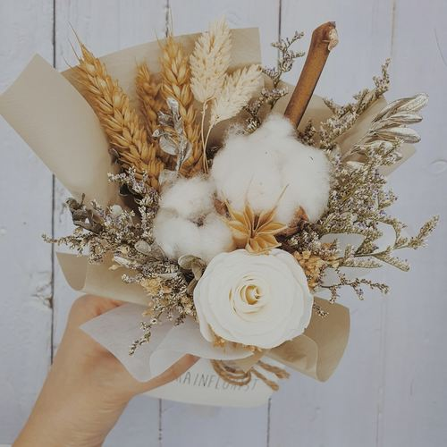 A brown bouquet of dried flowers and white rose.