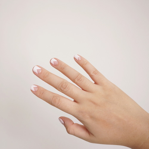 A female right hand with open palm showing nail wraps on her fingers. The nail wrap has a light pink base with a clear triangular bottom with white horizontal stripes.