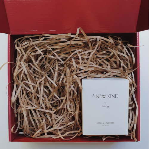 Red gift box filled with brown shredded paper. On the bottom right is a white box with the words A new kind of energy printed on it.