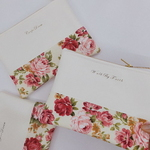 Three white leather clutches stacked on top of one another, each with a different quote printed in black. The clutches have floral prints on the bottom half and gold zipper.