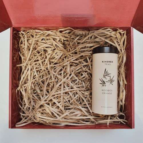 Red gift box filled with brown shredded paper. On the right is a pale orange cylindrical tin can with black lid. The tin is labeled Kindred Teas on top, with rooibos leaves in the middle and the words Rooibos Orange and 18 Pyramid Bags below.