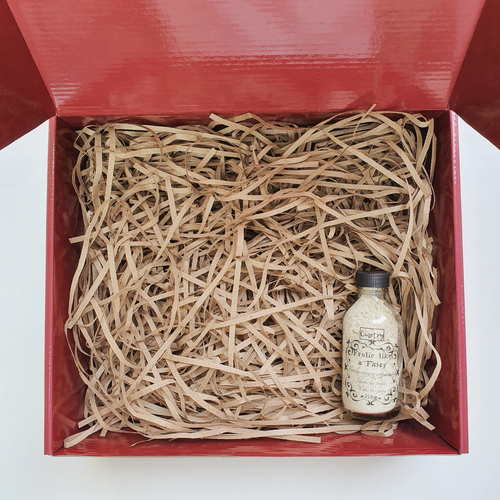 Red gift box filled with brown shredded paper. On the bottom right is a small transparent clear glass bottle with small flower petals spilling out from its tip. The bottle is filled with white powder and the words Ometry is printed on top and Frolic like a fairy is printed below.