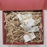 Red gift box filled with brown shredded paper. On the right is a blue bouquet of dried flowers and blue carnation.
