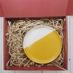 Red gift box with brown shredded paper. On the right is an 8 inch yellow and white porcelain plate.