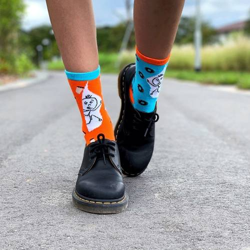 A model wearing a pair of socks and black shoes. The socks each has a different colour. The sock on the left foot is in light blue, coupled with orange colour cuff and toe. There are dark brown donut graphics spread all over the sock. The sock on the right foot is in orange colour, coupled with light blue cuff and toe. There are coffee graphics spread all over the sock. Both socks have a stick man graphic printed against a white background at the leg region.