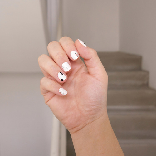 A female right hand with half-open palm showing nail wraps on her fingers. The nail wrap has five different design for each finger nail. The nail wrap has an off-white base with hand-drawn black lines and metallic rose gold print.