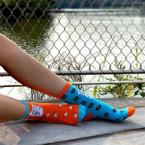 A model wearing a pair of socks, each with a different colour. The sock on the left foot is in light blue, coupled with orange colour cuff and toe. There are dark brown donut graphics spread all over the sock. The sock on the right foot is in orange colour, coupled with light blue cuff and toe. There are coffee graphics spread all over the sock. Both socks have a stick man graphic printed against a white background at the leg region.