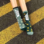 A model wearing a pair of socks, each with a different colour. The sock on the left foot is in dark green, coupled with light green cuff and toe. There are yellow toast graphics spread all over the sock. The sock on the right foot is in light green, coupled with dark green cuff and toe. There are eggs graphics spread all over the sock. Both socks have a stick man graphic printed against a white background at the leg region.