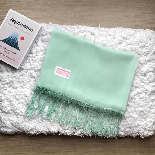 Folded light green shawl with fringes below. A small pink textile with white frame sewn on the left side of the shawl says Corporate Cuddles.