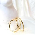 A pair of petite gold hoop earrings.