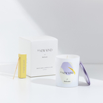 A white candle in the foreground with a purple cover leaning against it and a white candle box in the background with a yellow match box beside it. The candle is labeled with a hexagon sticker. The sticker has a white base with abstract prints in lavender and yellow. The words A new kind of delicate is printed on it. The same words can be seen on the white box behind.