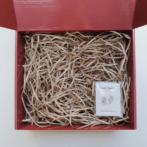 Red gift box filled with brown shredded paper. On the bottom right is a pair of clear rectangular stud earrings with blue and gold foil inside, wrapped in clear plastic.