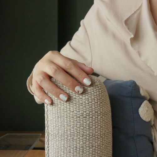 A female model wearing nail wraps on her right fingers. The nail wrap has a nude-coloured base with strokes in coral, light green and black.