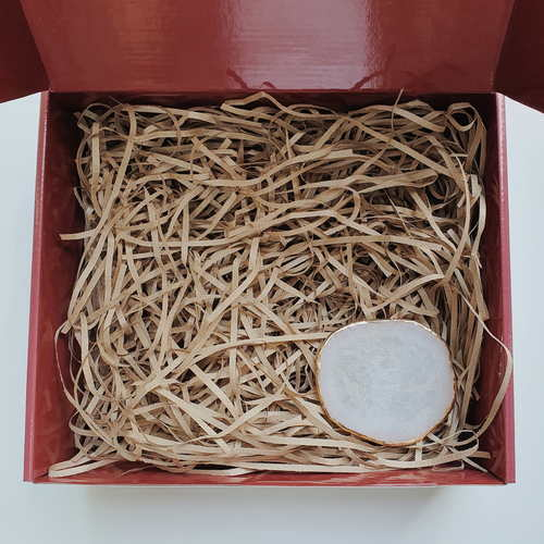 Red gift box filled with brown shredded paper. On the bottom right is a gold rimmed white agate coaster.