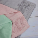Three shawls with fringes in light green, pink and gray are placed on top of one another.