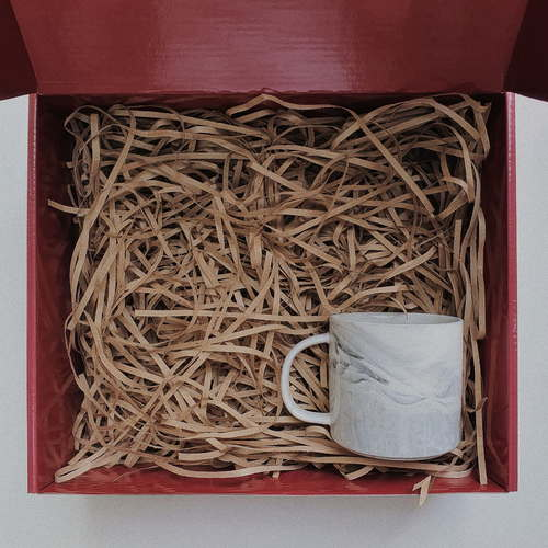 Red gift box filled with brown shredded paper. On the bottom right is a blue grey marbled mug with handle.