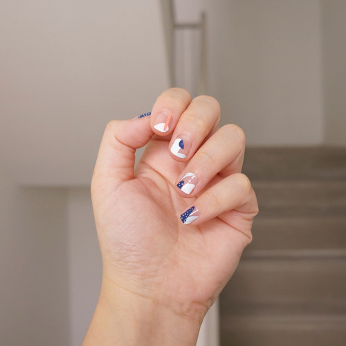 A female left hand with half-open palm showing nail wraps on her fingers. The nail wrap has five different design for each finger nail. The nail wrap has a clear transparent base with abstract patterns in solid blue, white and coral.