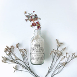 A small transparent clear glass bottle with small flower petals spilling out from its tip. The bottle is filled with white powder and the words Ometry is printed on top and Frolic like a fairy is printed below.