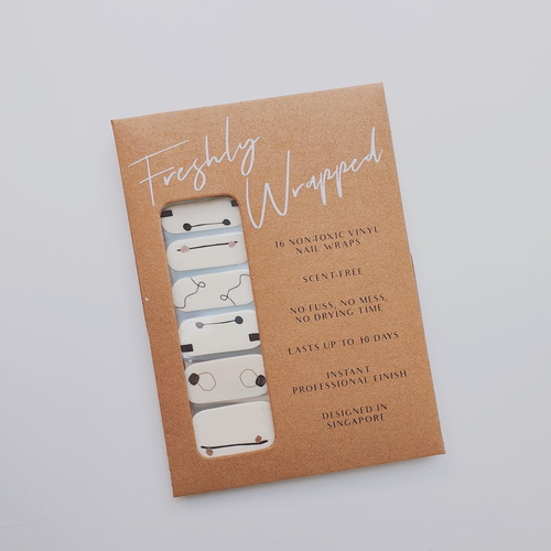 Brown rectangle paper packaging of a nail wrap. The nail wrap has five different design for each finger nail. The nail wrap has an off-white base with hand-drawn black lines and metallic rose gold print. The words Freshly Wrapped can be seen on top of the packaging.