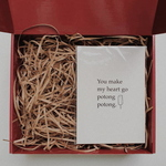 Red gift box filled with brown shredded paper. On the right is a white A5 card with the quote You make my heart go potong potong. and a graphic of a potong ice cream.
