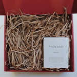 Red gift box filled with brown shredded paper. On the bottom right is a white box with the words A new kind of delicate printed on it.
