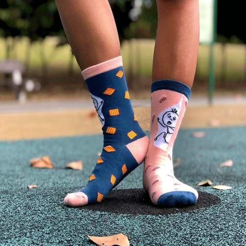 A model wearing a pair of socks, each with a different colour. The sock on the left foot is in salmon pink, coupled with dark blue cuff and toe. There are red, white and purple bacon graphics spread all over the sock. The sock on the right foot is dark blue, coupled with salmon pink cuff and toe. There are yellow waffles graphics spread all over the sock. Both socks have a stick man graphic printed against a white background at the leg region.