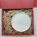 Red gift box filled with brown shredded paper. On the right is an 8 inch light blue and white porcelain plate.