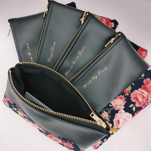 Five black leather clutches stacked on top of one another, each with a different quote printed in gold. The clutches have floral prints on the bottom half and gold zipper.
