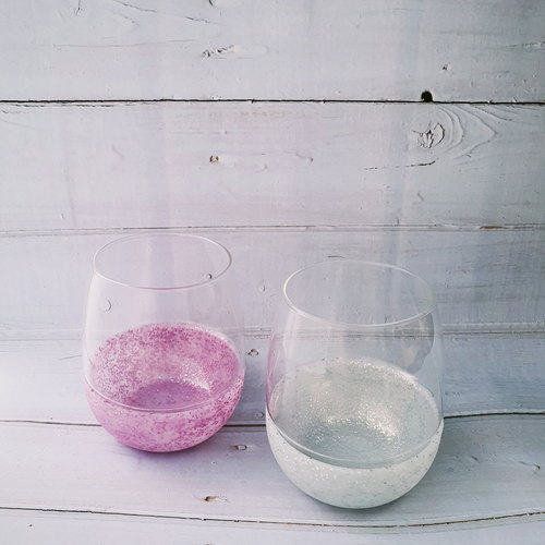 Two Stemless Wine Glasses with pink silicone glitter wrapped around the base of the left wine glass and white silicon glitter on the right.