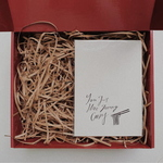 Red gift box filled with brown shredded paper. On the right is a white A5 card with the quote You got mee goreng crazy and a graphic of a pair of chopsticks picking up noodles.