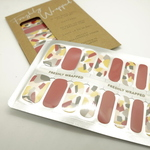 In the foreground is a set of nail wraps inside a clear plastic packaging. The nail wrap comes in two designs. The nails for the index finger and thumb are red while the rest of the fingers have an abstract brush pattern in white, yellow, light grey, dark grey and red. In the background is a brown rectangle paper packaging of the nail wrap. The words Freshly wrapped can be seen on top of the packaging.