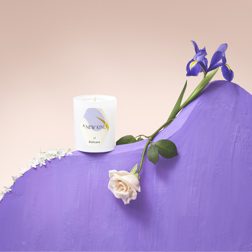 A white candle labeled with a hexagon sticker. The sticker has a white base with abstract prints in lavender and yellow. The words A new kind of delicate is printed on it.