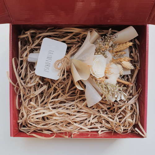 Red gift box filled with brown shredded paper. On the top half of the box is a brown bouquet of dried flowers and white rose.