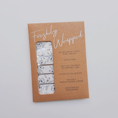 Brown rectangle paper packaging of a nail wrap. The nail wrap has a clear transparent base with fine blue and white porcelain floral. The words Freshly Wrapped can be seen on top of the packaging.
