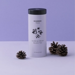 A purple cylindrical tin can with black lid. The tin is labeled Kindred Teas on top, with flowers in the middle and the words Elder and cream black tea and 18 Pyramid Bags below.
